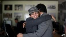 Hossaini (a la izquierda) es abrazado por un colega después de ganar el Pulitzer.